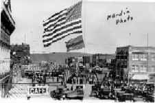 View of Main Street, Henryetta, Oklahoma on a holiday. Flags draped across the street