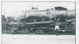 A picture of my father standing by the engine after it was set upright on the tracks.