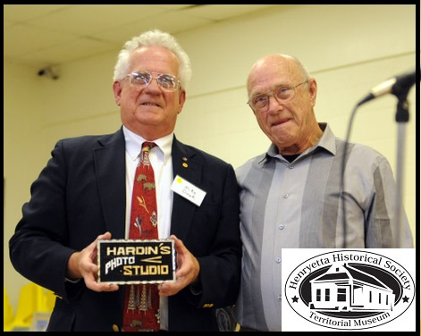 Mike Doak, president of the Henryetta Historical Society, pictured with Richard Walker, step grandson of Joseph W. Hardin, who presented a gift of a Hardin's Studio sign at the Founders' Day Celebration on November 16, 2013.